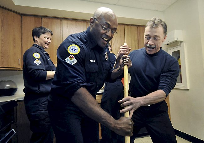 """St. Paul firefighter Billeigh Riser Jr. of St. Paul, center, is schooled in the art of floor mopping by his partner, Ron Nistler of Star Prairie Township, Wis., right, at Fire Station 23 in St. Paul on Monday, March 23, 2009. At left is Kelly McDougal. Recently returned from his second tour of duty in Iraq, Riser credits his """"extended family"""" of fellow firefighters with helping in his ongoing recovery from post traumatic stress disorder. (Pioneer Press: Richard Marshall)"""